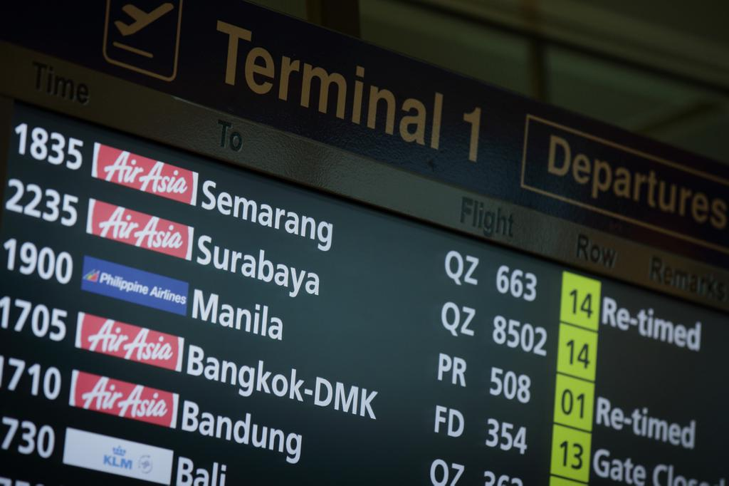 SINGAPORE - DECEMBER 28: An electronic flight information departure board showing information for AirAsia flights departing for Surabaya is seen at Changi Airport on December 28, 2014 in Singapore.  AirAsia announced that flight QZ8501 from Surabaya, Indonesia to Singapore lost contact with air traffic control on the morning of December 28.  (Photo by Suhaimi Abdullah/Getty Images)