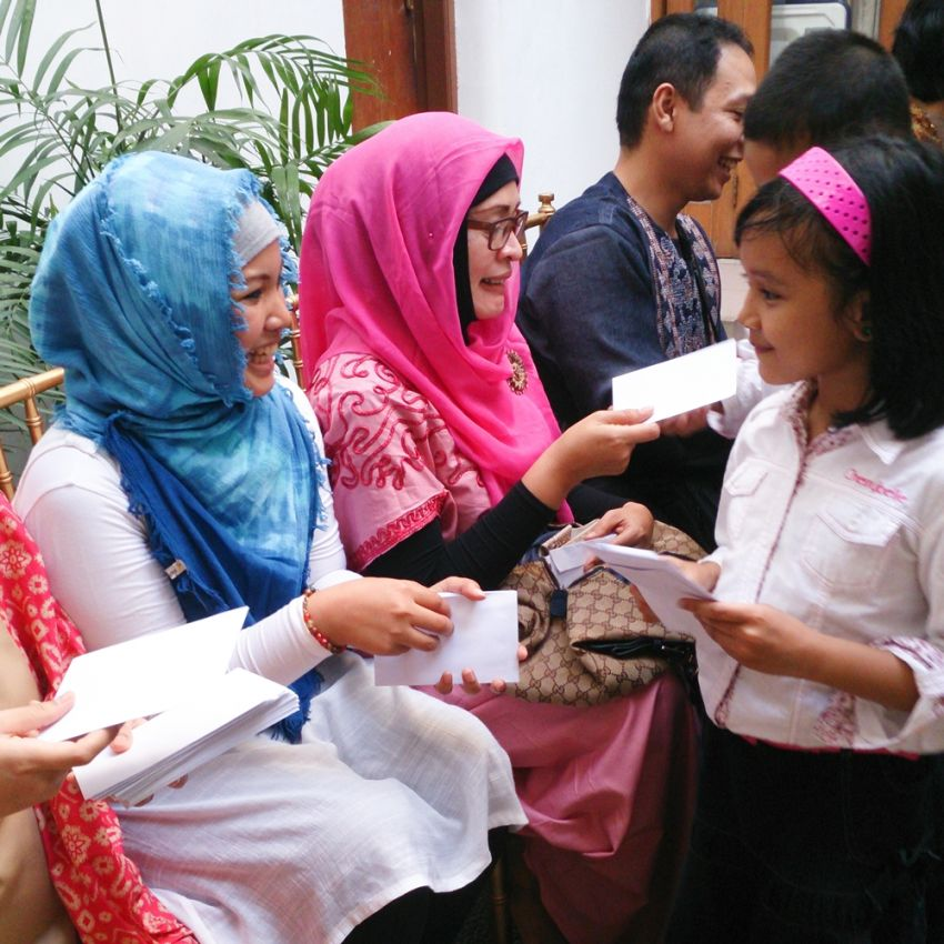 Child receiving Salam Tempel from her adult family members